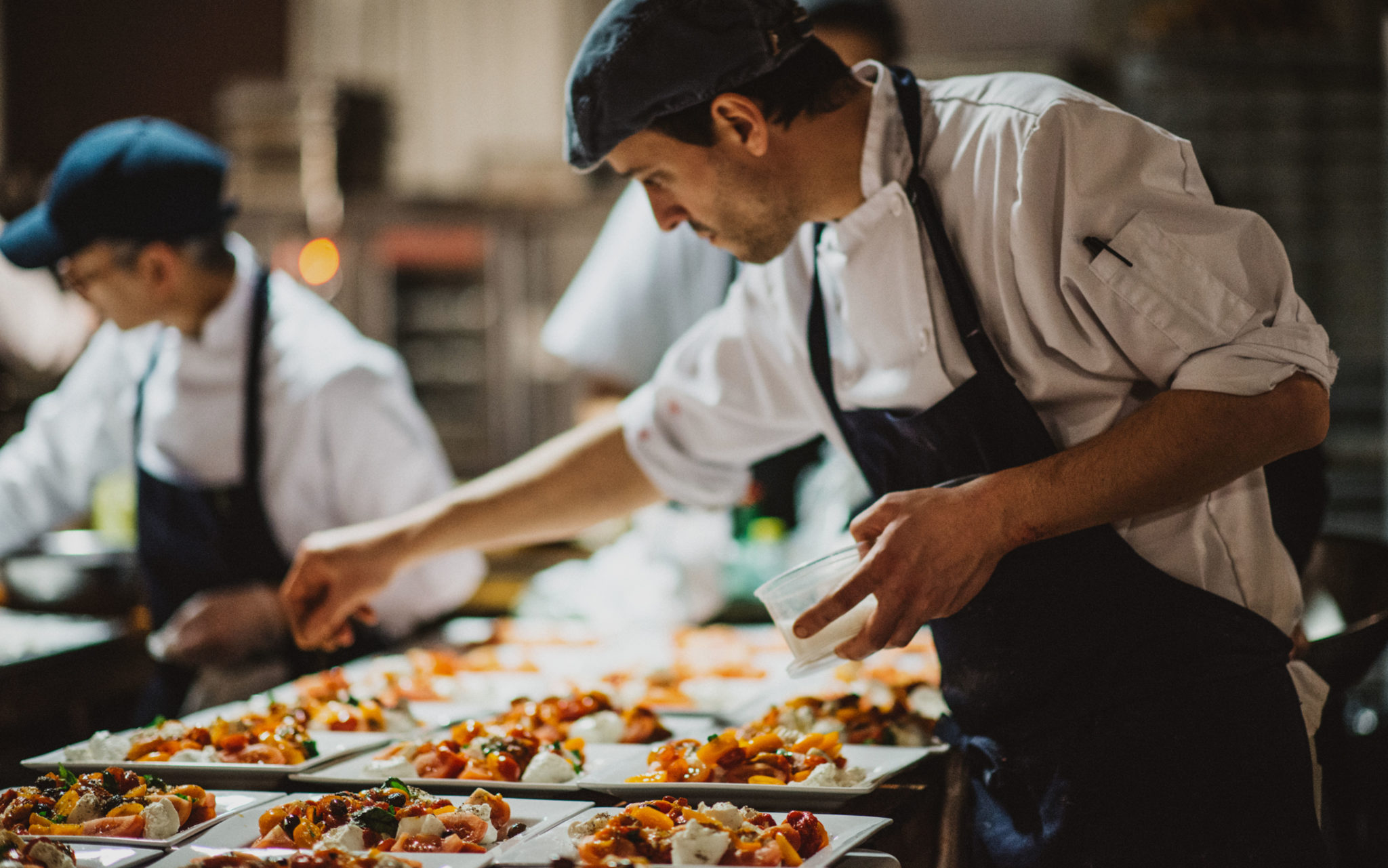 A sous-chef adding garnishes to dishes at Ristorante Beatrice.